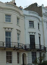Shows a photograph of two typical Regency houses with laurel wreath designs above the first floor windows.
